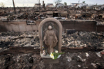 Flowers were laid in front of the statue of the virgin mary that survive the massive fire caused by hurricane Sandy in Breezy Point, New York on Friday,  November 2, 2012.