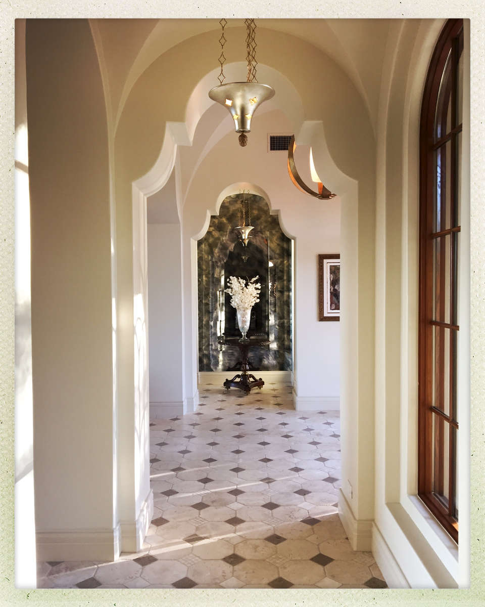 A classic floor pattern enriched with polished and honed travertine, porcelain grids, and pinto limestone accents.