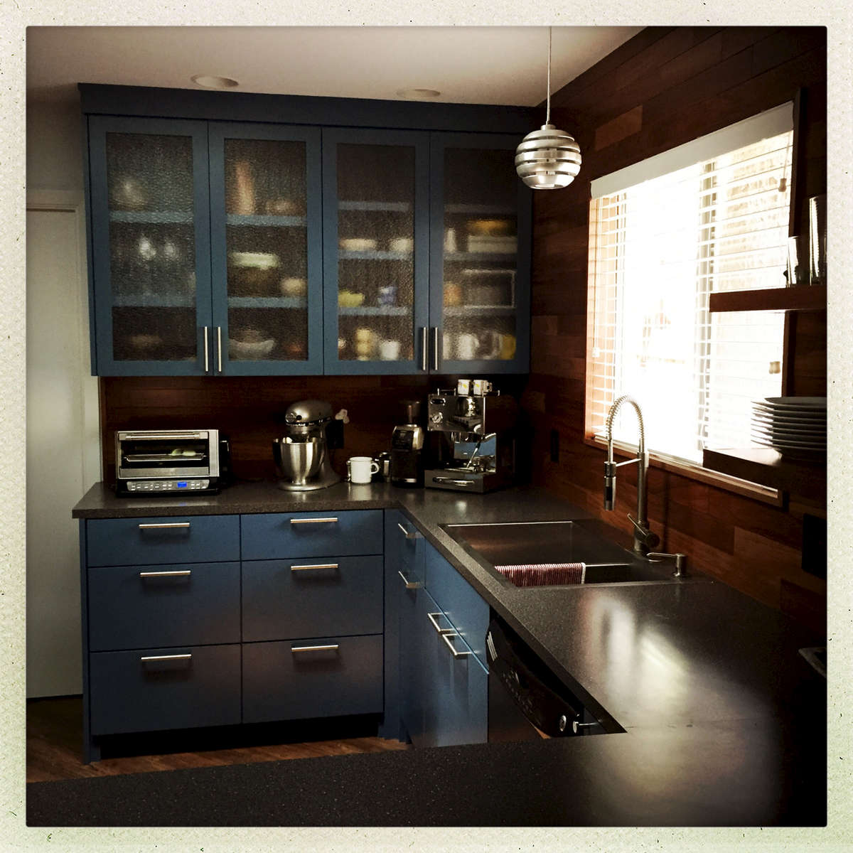 Blue delivers personality to this retro-house kitchen.Note the Brazilian hardwood backspalsh.