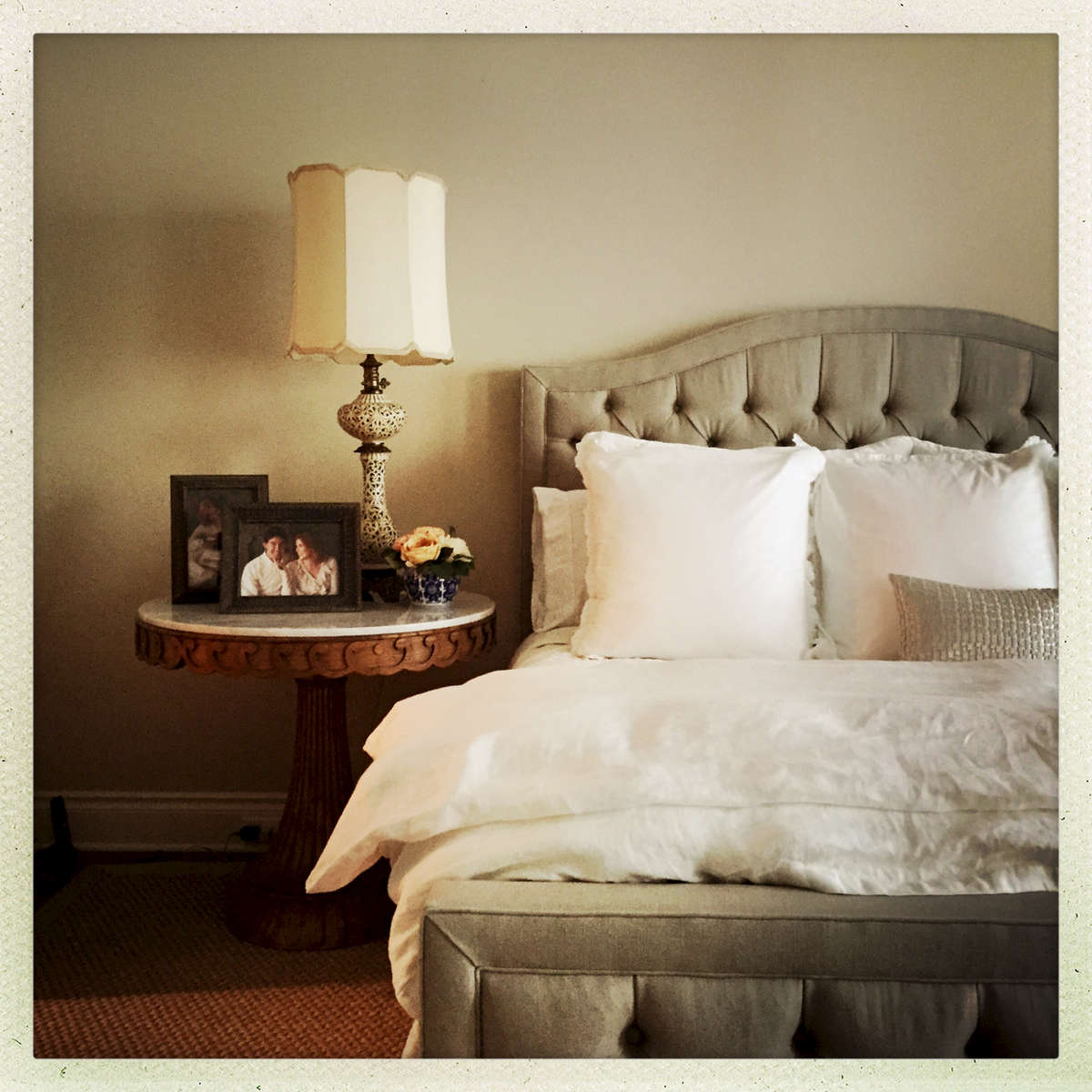 A custom linen bed and a scrolled marble-topped table to hold grandmother's lamp...cosy.