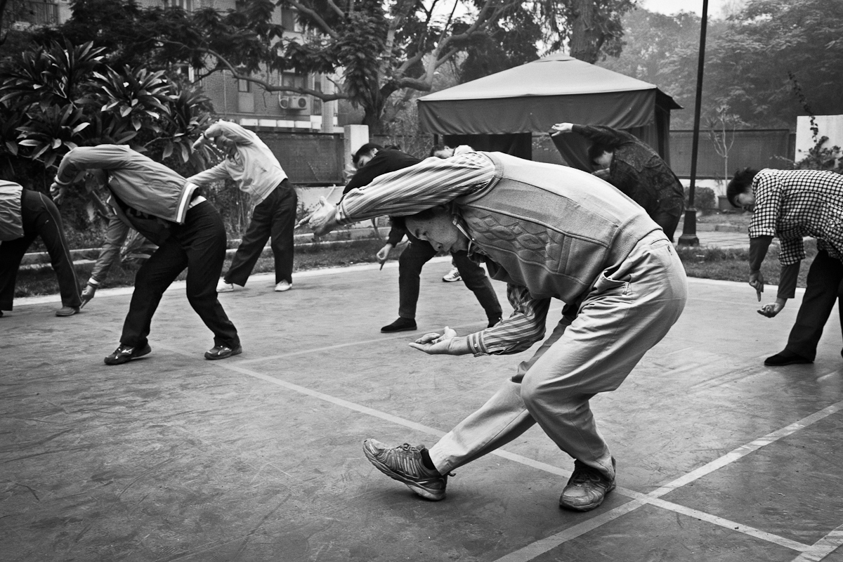 CAIRO, EGYPT - DECEMBER 20 :  Xi Ho Ling practices early morning Tai Chi with local Chinese in a public tennis court in Maadi on December 20, 2011 in Cairo, Egypt.