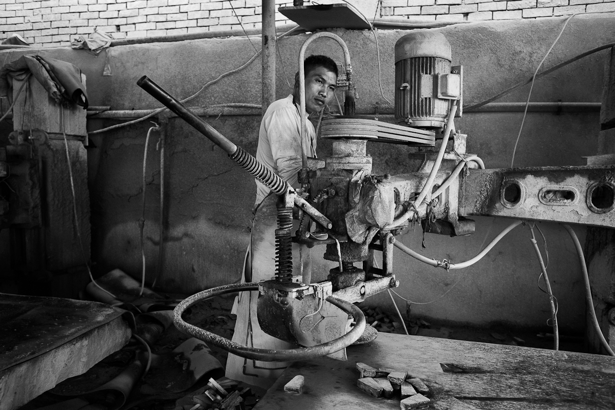 HELWAN, EGYPT - JUNE 18: Chinese employee repairs industrial machine at a Egyptian granite yard on June 18, 2012 in Shak El Thoaban, in Helwan, Egypt.