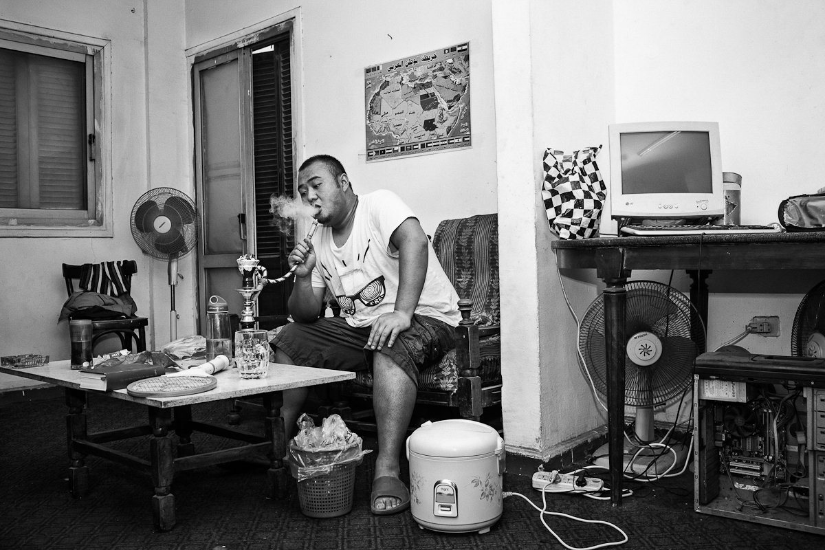 CAIRO, EGYPT - MAY 3 : Chinese Al-Azhar student, Lua Ma, who goes by his Muslim name of {quote}Rageb{quote} waits on his rice cooker while smoking a water pipe at home on May 3, 2012 in Moalin el Ara, in the periphery of Cairo.