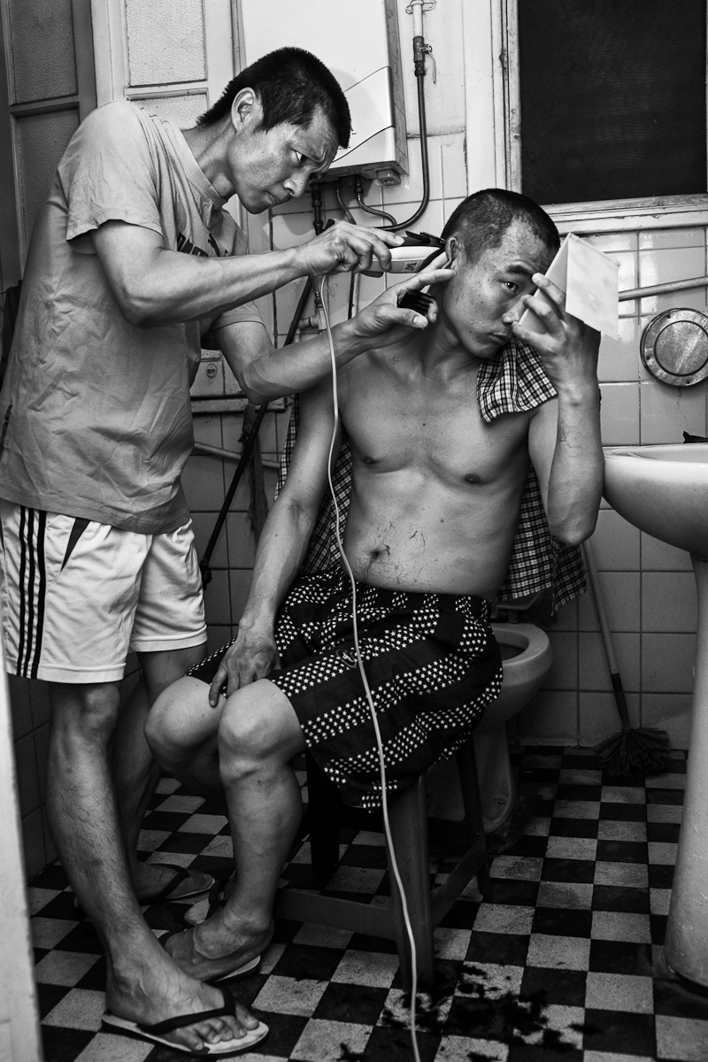 CAIRO, EGYPT - MAY 31 : Wu Qing Quan helps his brother in law Qing Gui cut his hair in their modest apartment shared with their wife's and many other Chinese street vendors on May 31, 2012 El Geish Square in Cairo, Egypt.