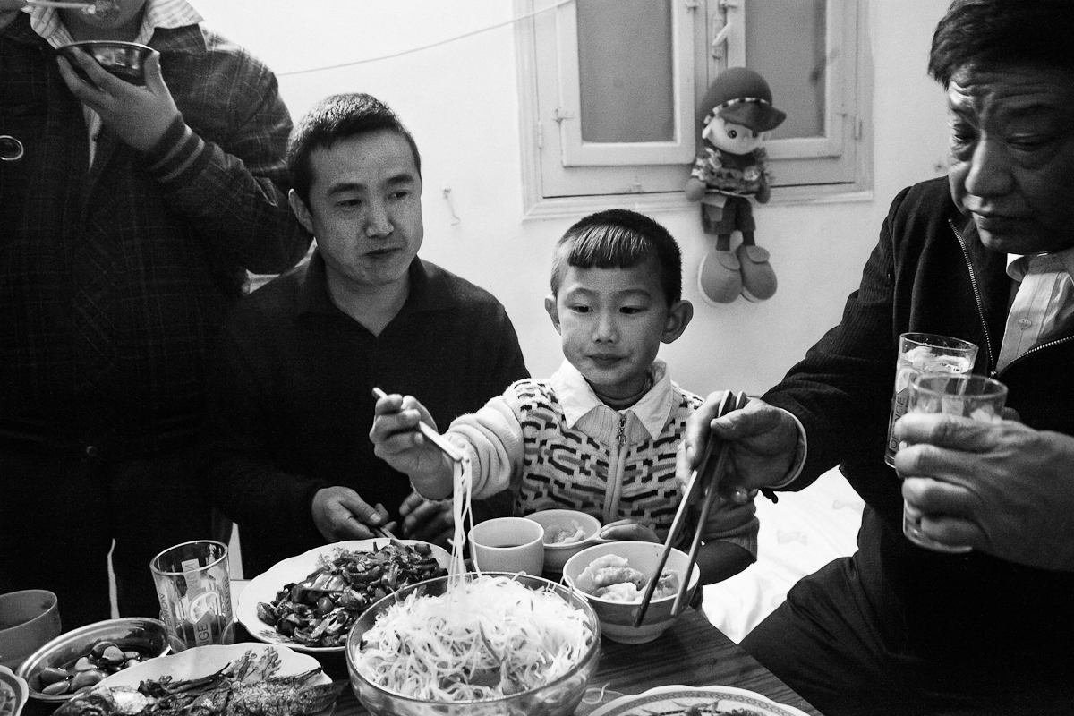 CAIRO, EGYPT - JANUARY 22 : Fubiao Ai, Zixin Ai, and Jingy Ai share the tradition homemade Chinese noodles at their home in celebration for Chinese New Years on January 22, 2012 outside Cairo, Egypt. Zixin Ai hair was cut in the {quote}dragon-style{quote} in honor of the Year of the Dragon.