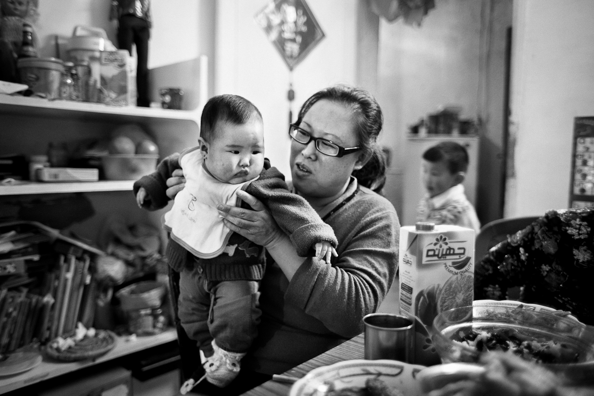 CAIRO, EGYPT - JANUARY 22 : Yuzhi Zhou hold hers her daught Ziqi Ai as they share the tradition homemade Chinese meal at their home in celebration for Chinese New Years on January 22, 2012 outside Cairo, Egypt. Ziqi Awas born in Egypt, despite China's one child policy.
