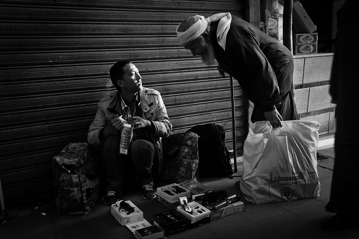 CAIRO, EGYPT - FEBRUARY 10: Li Ming, an illegal Chinese migrant worker sells blowdryers, cellphones and tasers on Tahrir Street despite the unrest just a block away on February 11, 2011 in Cairo, Egypt. Selling everything from plastic jewelry to fake iPhones, illegal migrant workers came to Egypt specifically in an effort to send money to their families back in China. Unfortunately, in light of the Egyptian uprising, this in itself has been a struggle for this community.