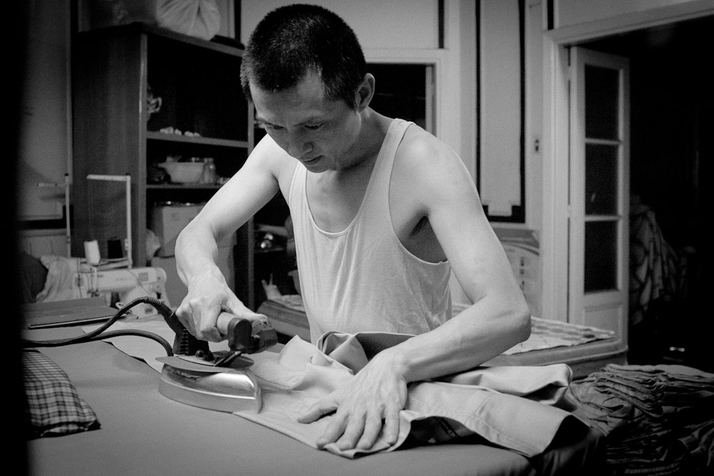 CAIRO, EGYPT - MAY 31 : Wu Qing works at a apartment sweatshop, where he can make about 300 hundred pairs of khakis in one ten hour night, on Medan El Geesh in Cairo, Egypt.