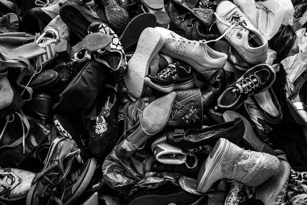 Donated shoes, are left unpaired on the top floors of a refugee non-for-profit. There is strangely always an abundance of adult supplies but a lack of children's clothes, alientation , canned and powder goods, such as milk.