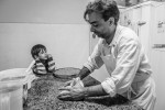Nour watches as his father Ayman prepares Syrian pasteries in their new home on the outskirts of São Paulo. Nour recalls as this entire family spent 17 days at sea in summer of 2015, and how his father, make risotto with salt water. Bound for Italy, their boat was intercepted by the Egyptian authorities, who arrested all 227 people onboard. The Syrian embassy refused to repatriate the family, so they applied for asylum to Brazil. Ayman, a resourceful 41 year old father of 2, say, {quote} In Brazil we are neither Shiete, or Sunni, Muslim or Christian. Veil or not. We are human. And so, I am happy.{quote}
