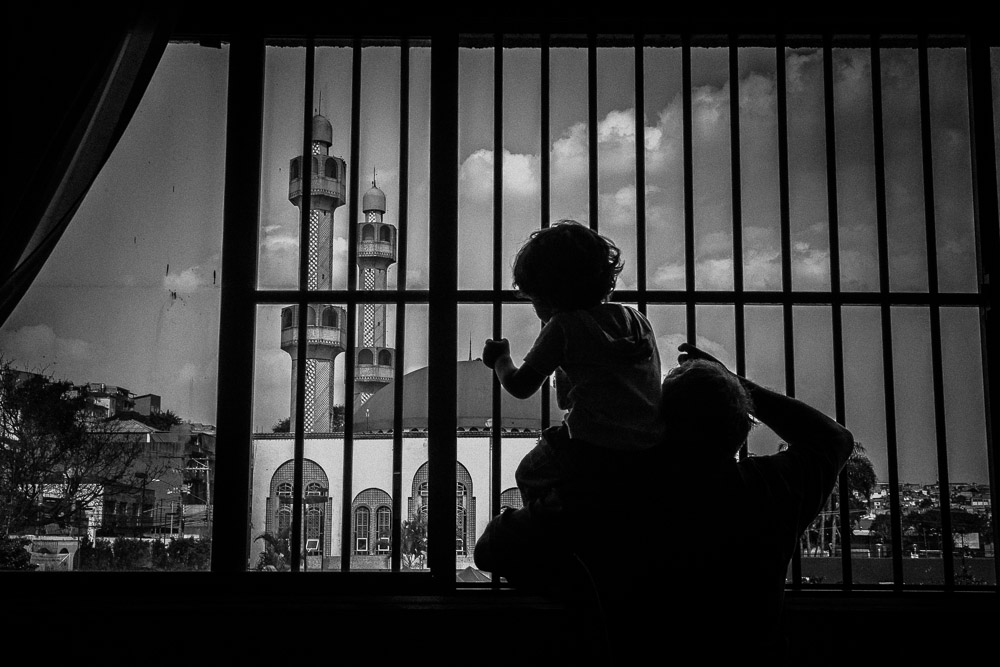 A Syrian refugee hold his son on his shoulders as they over look Santo Amara mosque and neighboring favela or slum on this hills in São Paulo.