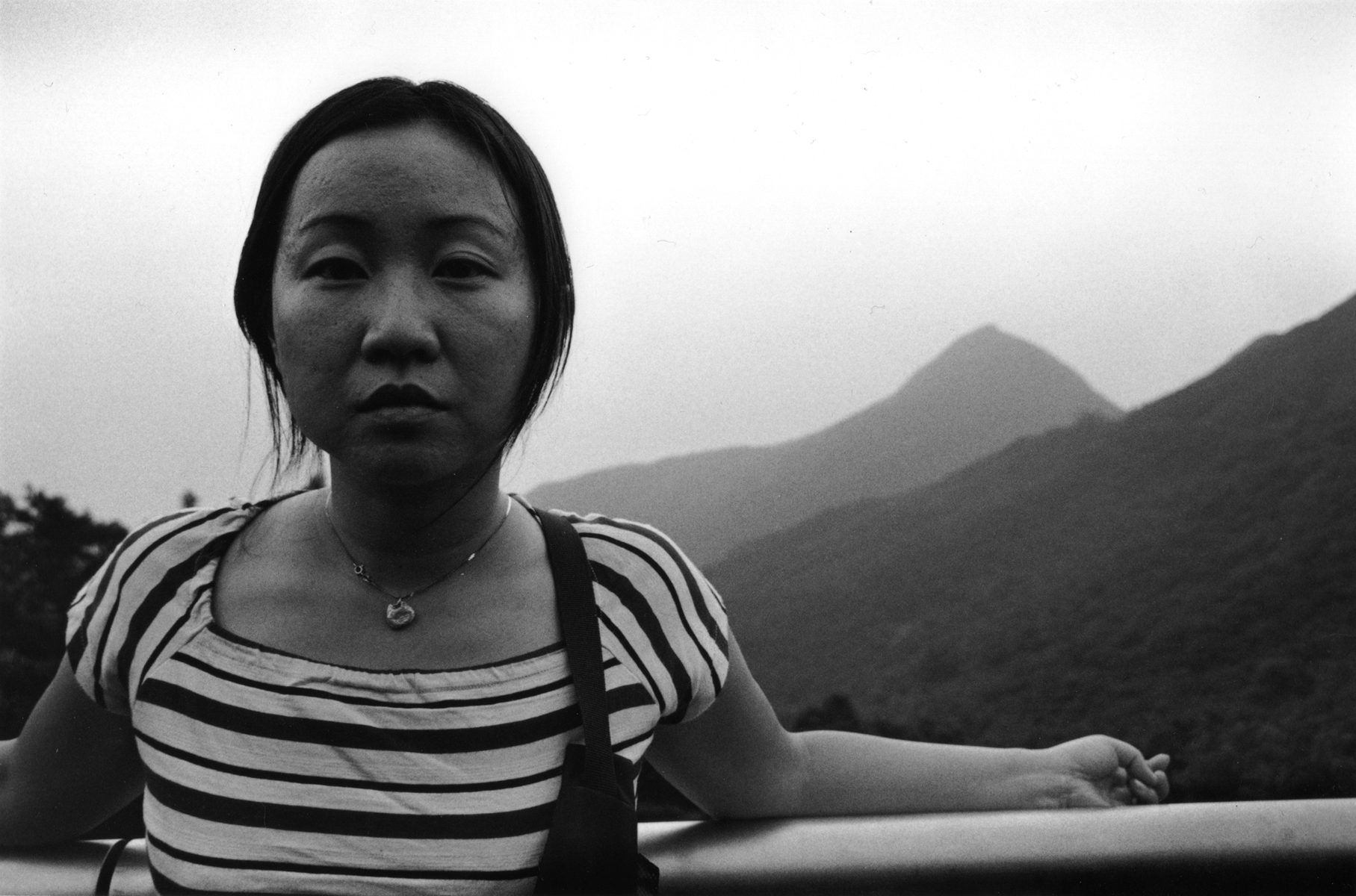 Chi Ying stands on top of Fung Wong Shan Peak Overlooking Hong Kong.Hong Kong Island