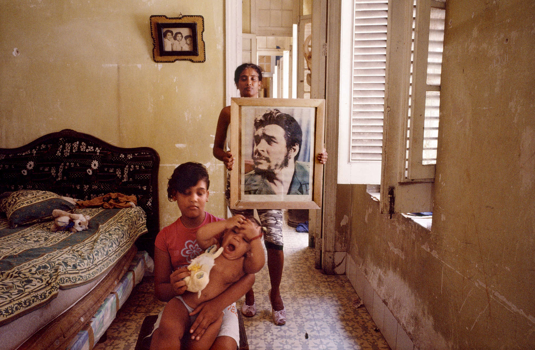Chavela poses for her protrait while holding her cousin. Her mother, in the back, holds an image of Ernesto Che Guevara, who was a major figure of the Cuban Revolution, and has become a symbol of rebellion througout the world. Havana, Cuba
