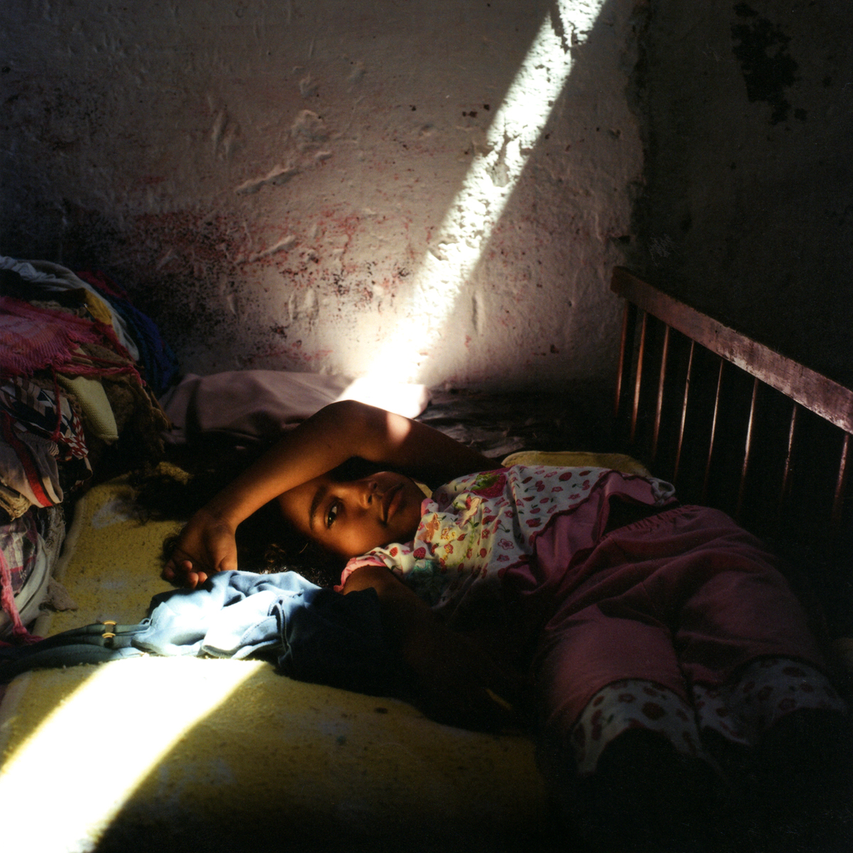 Hamilie, Enmanuel's sister, rests as the morning light pierces through a small piece of plastic, covering the windowabove.Havana, Cuba