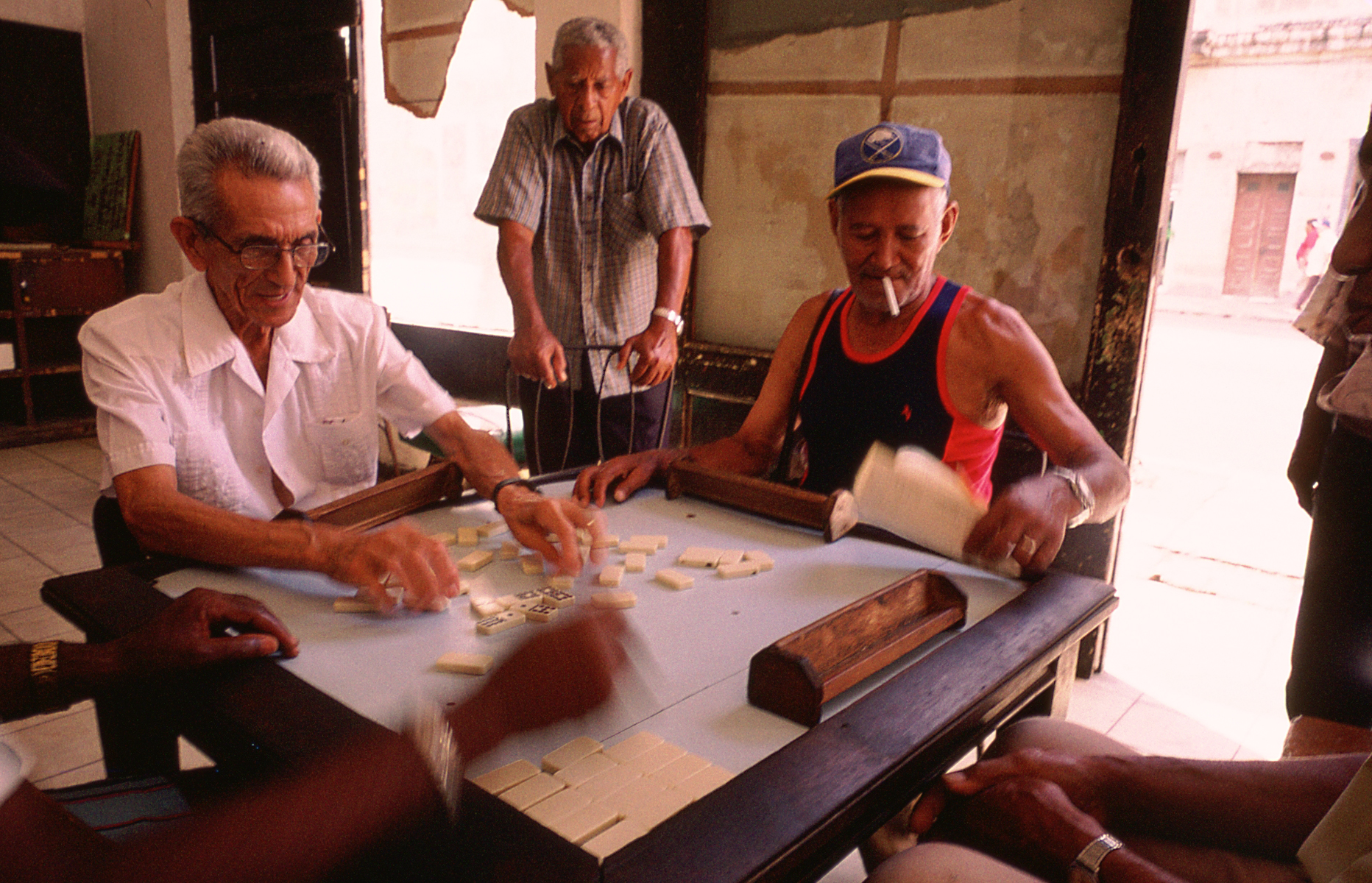 A group of elderly men gather in vacant building for an afternoon of dominoes and conversation. Havana, Cuba