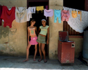 Two girls washing and hanging the clothes to dry, stop their work to have their porttaits taken. Havana, Cuba