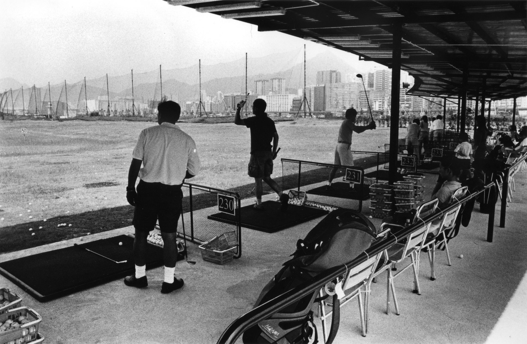 Hong Kongers enjoy an afternoon on the driving range of the once infamous Hong Kong Kai Tak International Airport. The story of Kai Tak started in 1922 when two businessmen Ho Kai and Au Tak formed the Kai Tak Investment Company in order to reclaim land in Kowloon for development. The land was acquired by the government for use as an airfield after the business plan failed. In 1924, Harry Abbott opened The Abbott School of Aviation on the piece of land. Soon, it became a small grass strip airport for the RAF and several flying clubs which, over time, grew to include the Hong Kong Flying Club, the Far East Flying Training School, and the Aero Club of Hong Kong which exist today as an amalgamation known as the Hong Kong Aviation Club. In 1928, a concrete slipway was built for seaplanes that used the adjoining Kowloon Bay which can be seen in old photographs. The first control tower and hangar at Kai Tak were built in 1935. In 1936, the first domestic airline in Hong Kong was established.Hong Kong Island