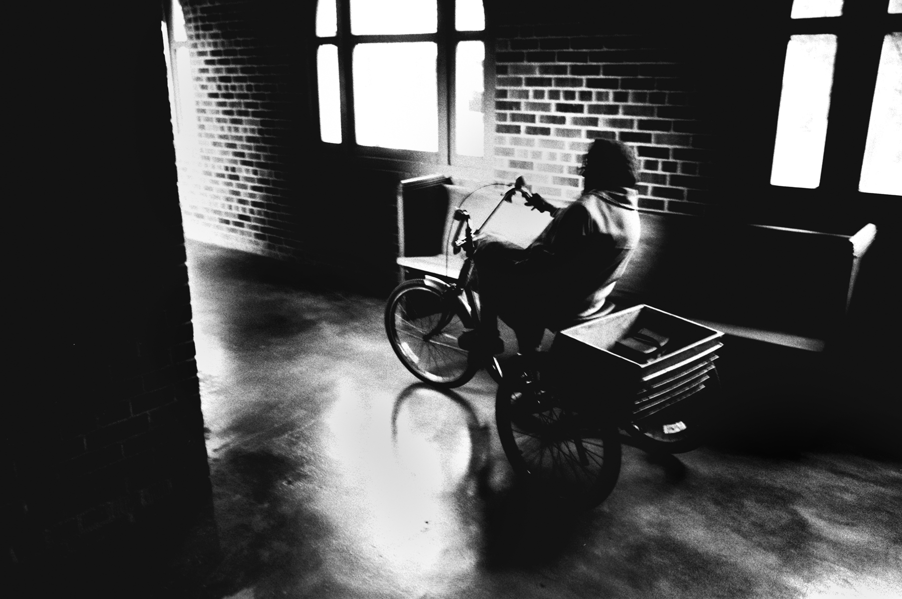 Betty Martin rides her bike through the long breezeways and corridors at Carville.