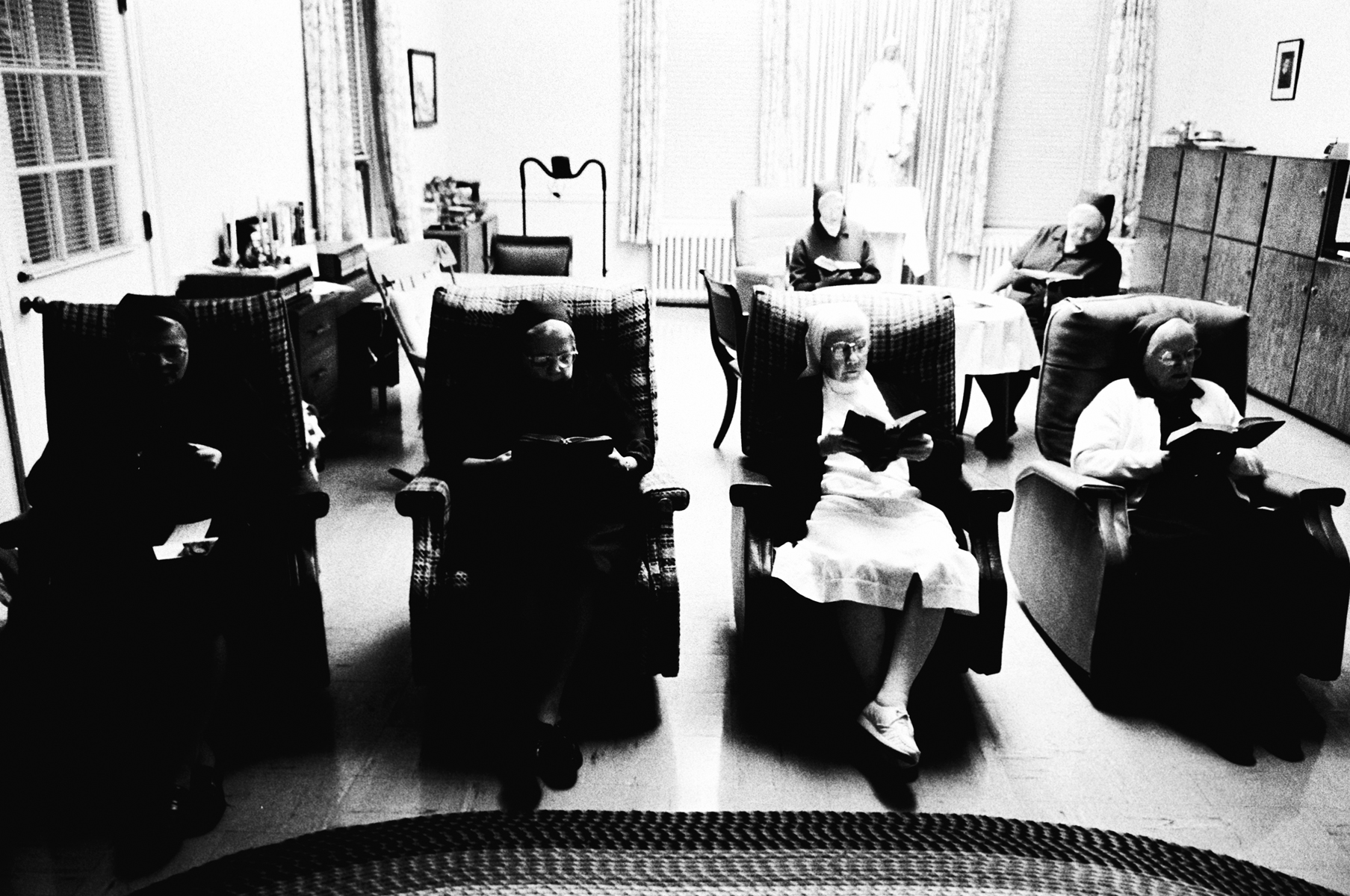The Daughters of Charity of St. Vincent de Paul sit in their lazy-boy chairs, while reading excerpts of the bible together.  In 1894, Dr. Isadore Dyer established the facility in Carville, and arranged a contract with the Daughters of Charity, who have served at the New Orleans Charity Hospital for 60 years, to provide the new facility with nursing services and domestic managment. In 1896, the first four sisters arrived to up their duties at Carville, beginning a tradition that continues to the present.