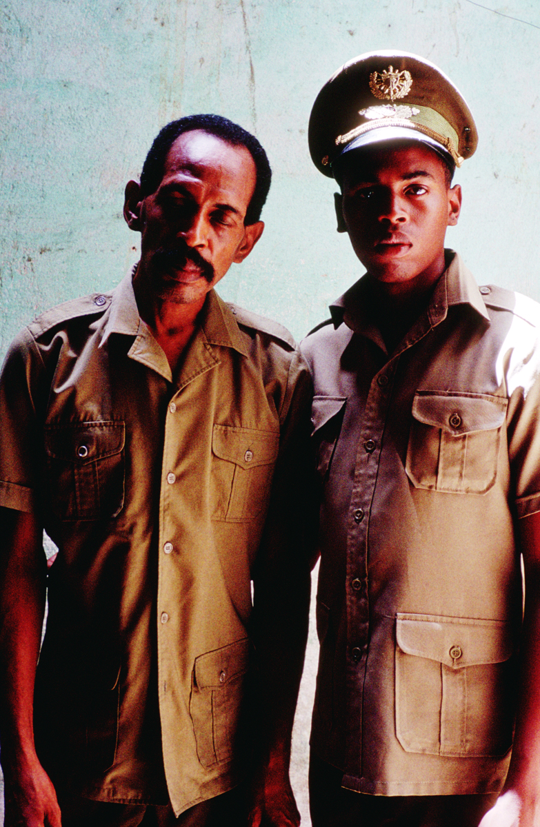 Father and son and pose in their military uniforms. the father has long retired from military service due to health concerns. His son is completing his second year of military service for the preparation and defense of Cuba. Havana, Cuba