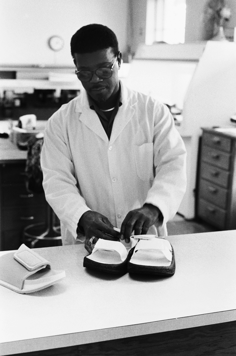 A worker at Carville, shapes and design shoes for each patient's needs to help further protect their feet from injury or further infection.