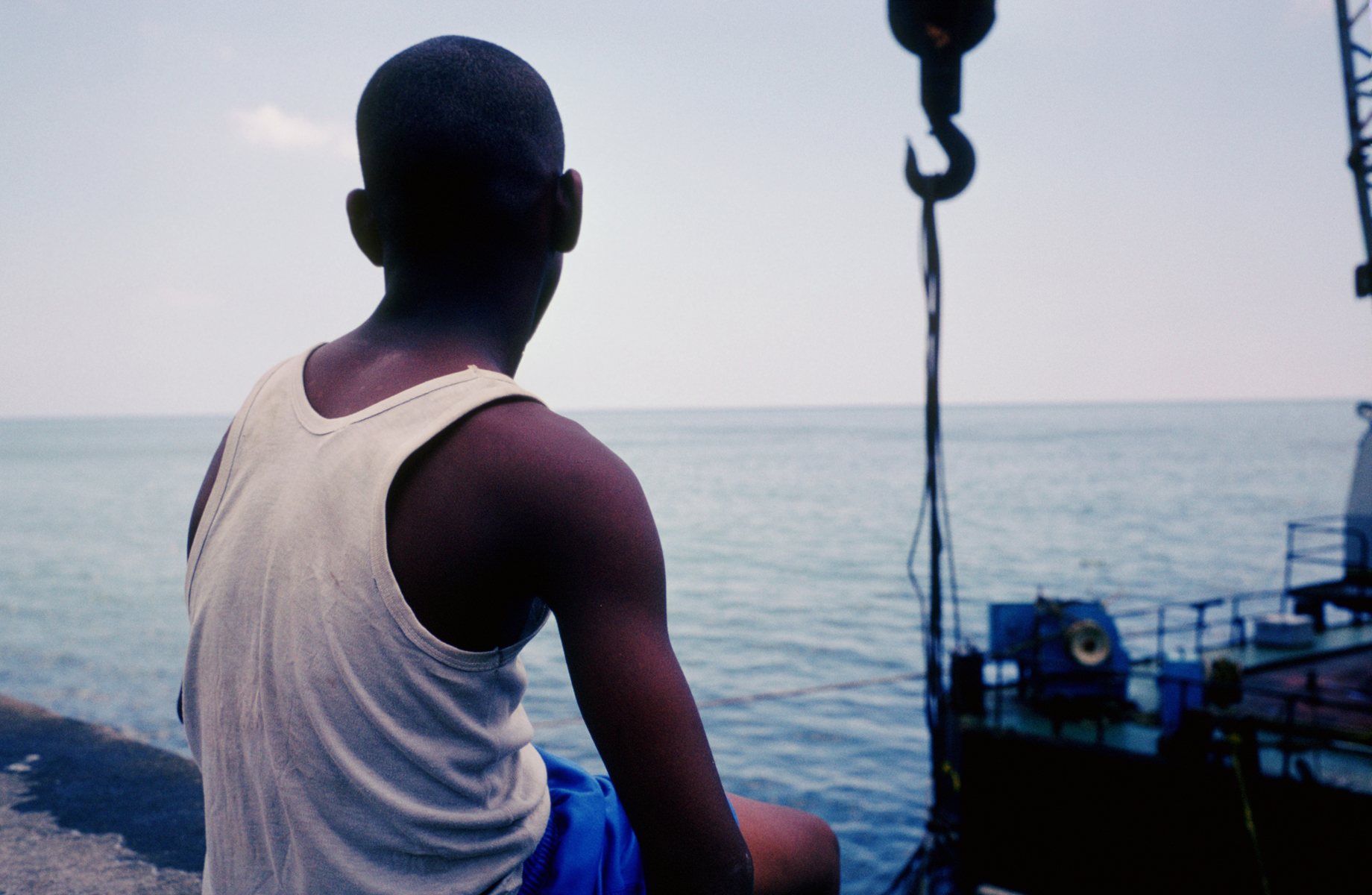 A boy sits on a ledge along the Malecon, watching men working and scuba diving from a barge. Havana, CUba