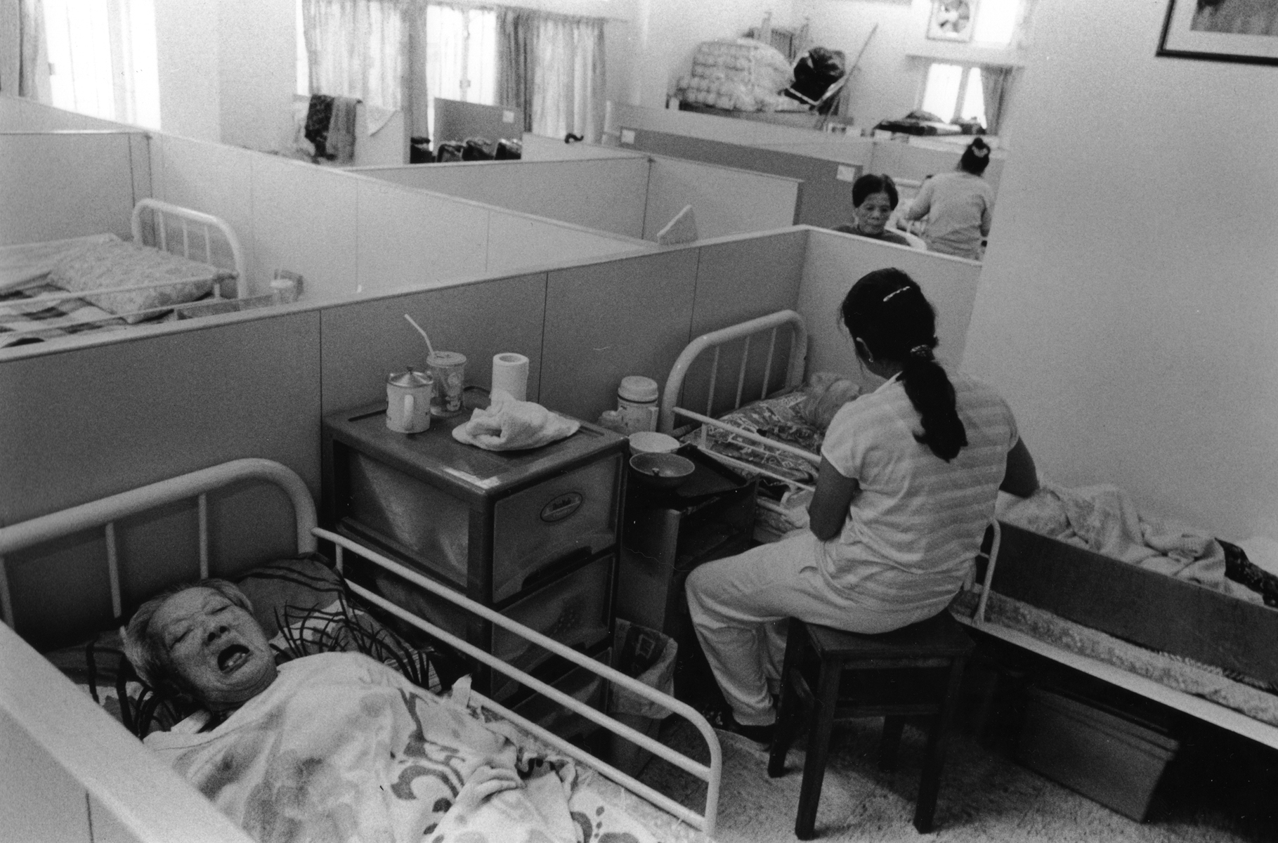 An elderly woman, whose family decided to place their relative in a nursing home, shares a cubicle with another patient, who is being fed by an attendant. Traditionally, the elderly will live with their children and grandchildren. However, as the younger generation have greater access to a college education and corporate jobs, many choose to place their elderly relatives in nursing homes for twenty-four hour care. Aberdeen Harbour, Hong Kong