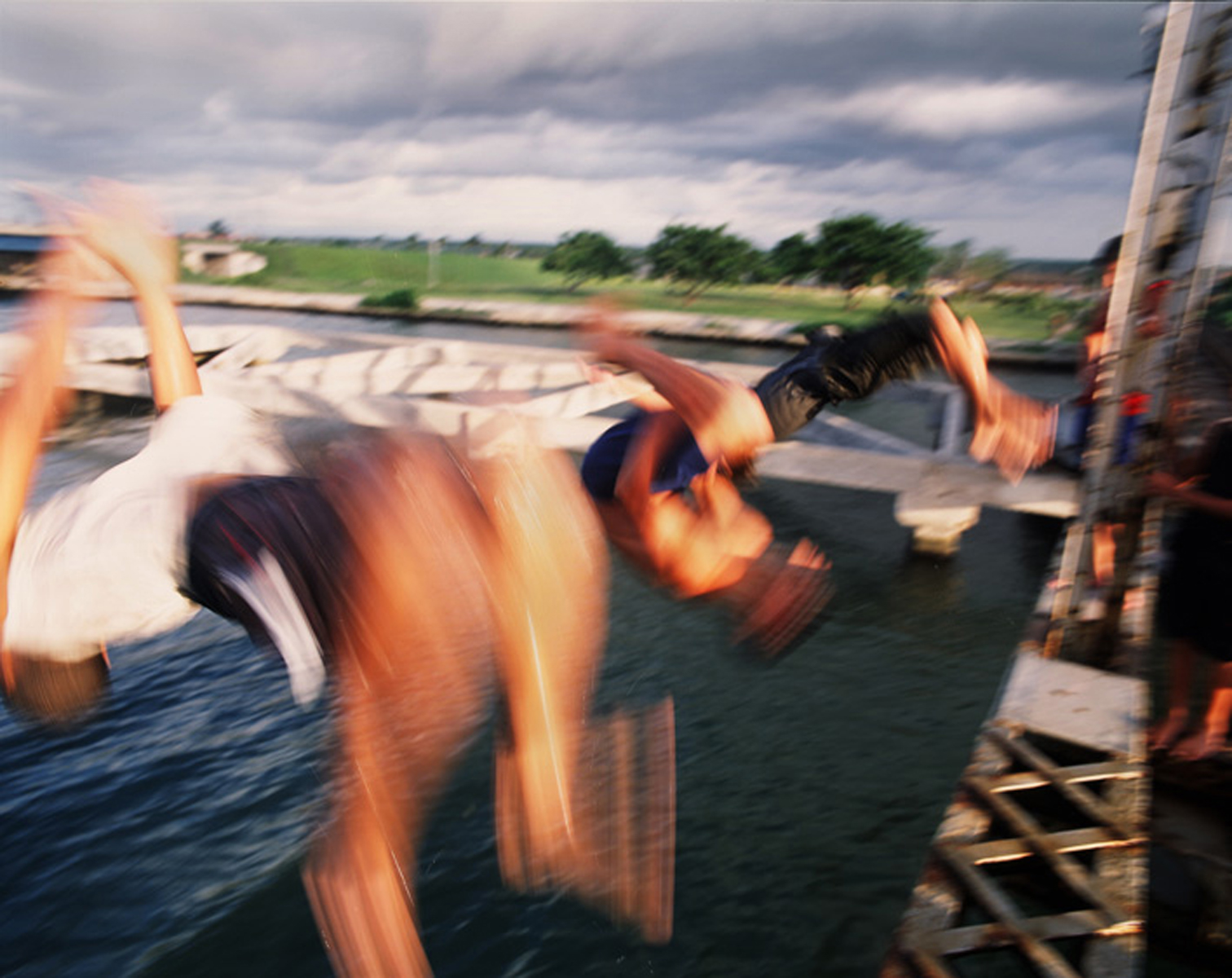 Three Teenage boys synchronize their backflips as they jump off a railway brdige into the waterway below. Both the railway bridge and waterway are used for commerical purposes by freight trains and commercial cargo ships. These teenage boys jump and swim at their own risk due to a lack of laws, police enforcement, or opportunites for jobs or educational summer programs.Mantanzas, Cuba