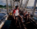 A teenage boy adjusts himself, while the other boys sit and talk, while resting or wating for their turn to jump from the railway bridge into waterway below. Both the railway bridge and waterway are used for commerical purposes by freight trains and commercial cargo ships. These teenage boys jump and swim at their own risk due to a lack of laws, police enforcement, or opportunites for jobs or educational summer camps.Mantanzas, Cuba