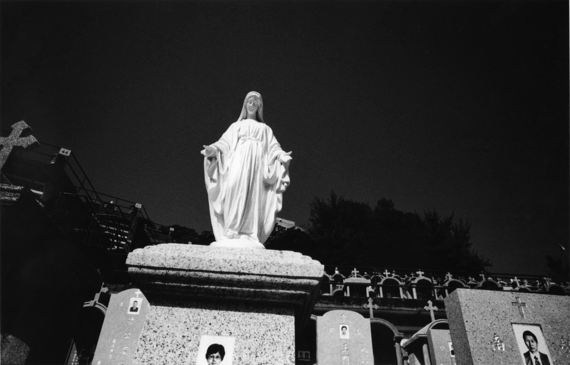 A statue of the Virgin Mary sits on a tomb, overlooking the Cheung Sha Wan Catholic Cemetery. Hong Kong Island