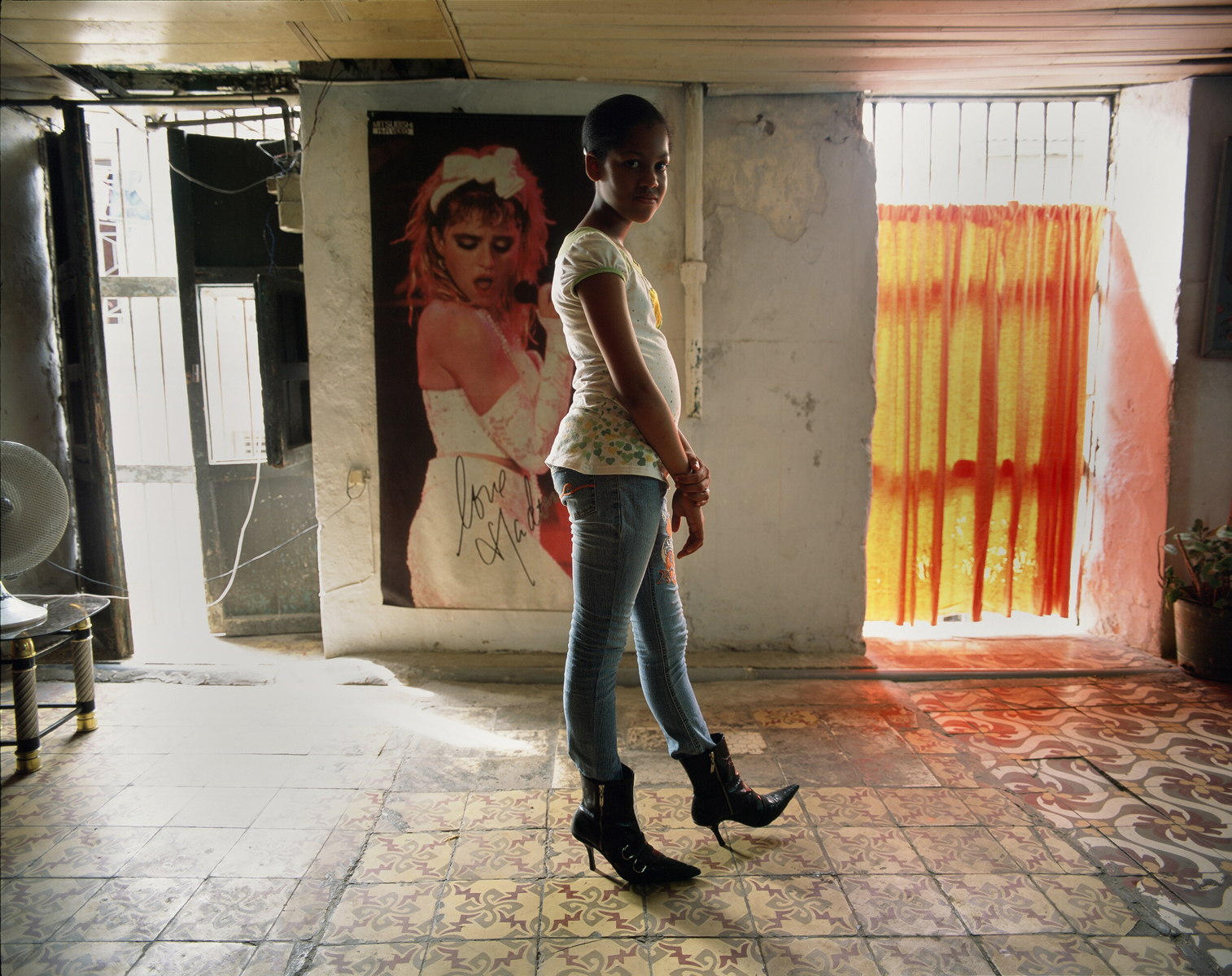 Nazarena, who kept chasing me around the neighborhood for days, asking me when I will photograph her again? She wanted to be photographed wearing her new boots, in front of Madonna.Havana, Cuba