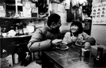 A father enjoys a bowl of noodles with his daughter. Kowloon Peninsula, Hong Kong