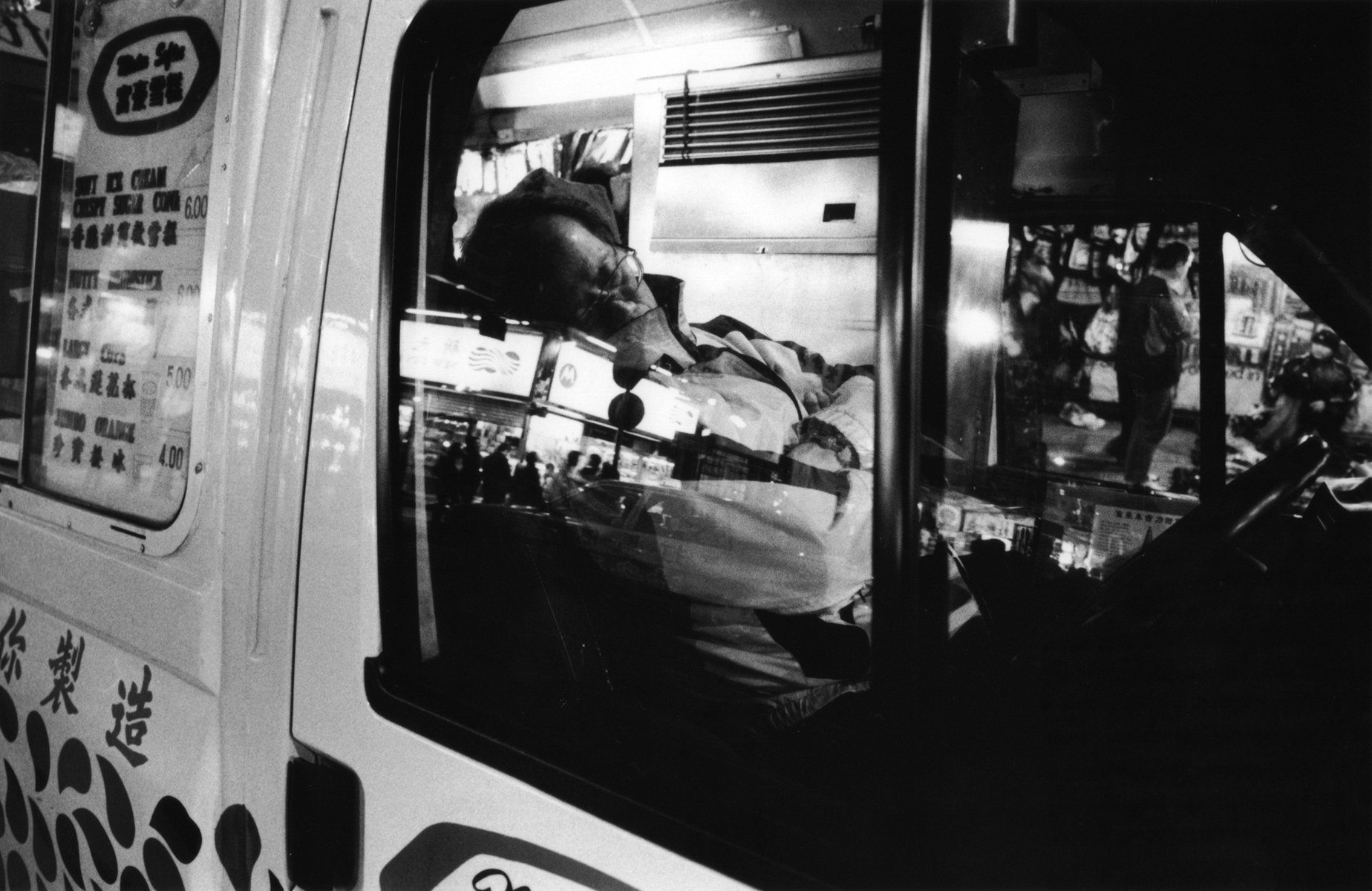 A late night vendor sleeps in his van in Mong Kok, while wating for residents and night market shoppers to knock and buy ice cream.Kowloon Peninsula, Hong Kong.