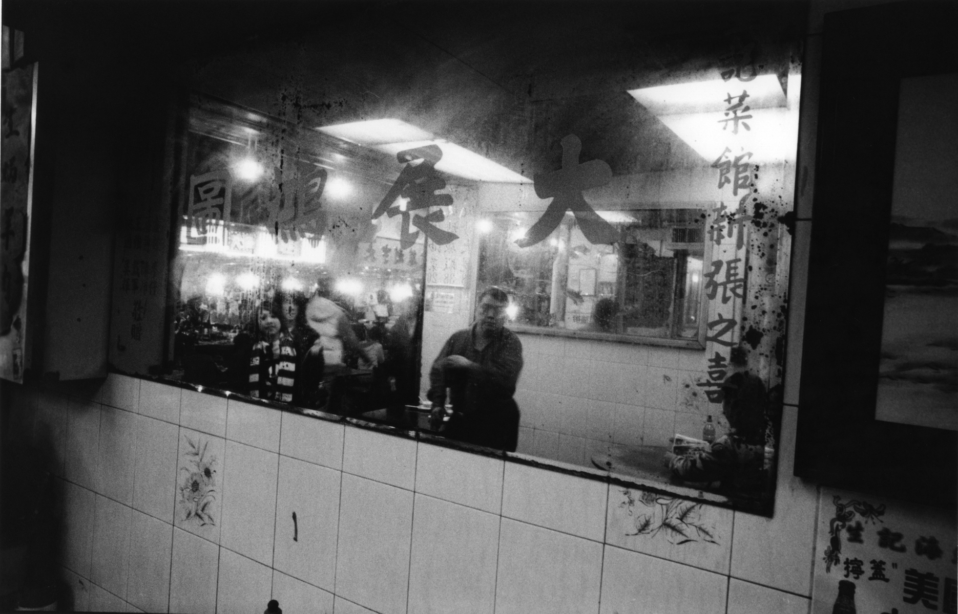 One of the many popular, late nitght destinations, offering inexpensive delights for residents and night market shoppers in Mong Kok. The engraving on the mirror, {quote}Spread Your Wings,{quote} is believed to reflect around the restaurant, bringing prosperity and good fortune to the owner.Kowloon Peninsula, Hong Kong.