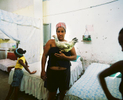 Lelani holds her pet chikcen while her two daughters, Kailey (left) and Hamilie (right), play in their home. Havana, Cuba