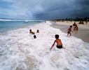 Children playing in the waves at Playa del Este, a popular beach for Cubans, 45 minutes east of Havana province. Playa del Este, Cuba