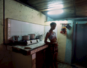 Nazarena, prepares dinner,--chicken, rice, and black beans--in a makeshift kitchen, with dripping water, a hotplate, and two pots. Despite her stark surroundings and limited resources, she is always smiling and listening to music whiling preparing a feast. Havana, Cuba