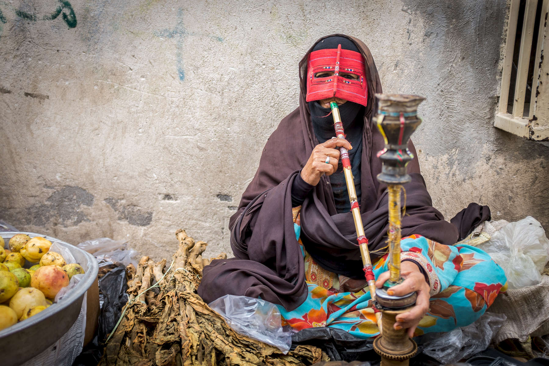 A woman vendor smoking tobacco from a waterpipe or 'nargeela' in Persian.   This practice is now banned for women throughout Iran in public places, though it remains popular amongst the vendors at the weekly Panjshambe Bazar, Minab, who can be found discreetly puffing away in corners of the market.