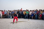 A young girl chases a python let loose at a sideshow performance in Bandar Abbas.  The city is positioned overlooking the Strait of Hormuz and the entrance to the Persian Gulf.