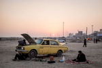 Men working to fix an Iranian built Paykan Taxi as the sun sets over Bandar Abbas on the Persian Gulf Coast of Iran.   On returning to the city a week after this was shot, the men were still working on the cab, seemingly no closer to getting it moving.