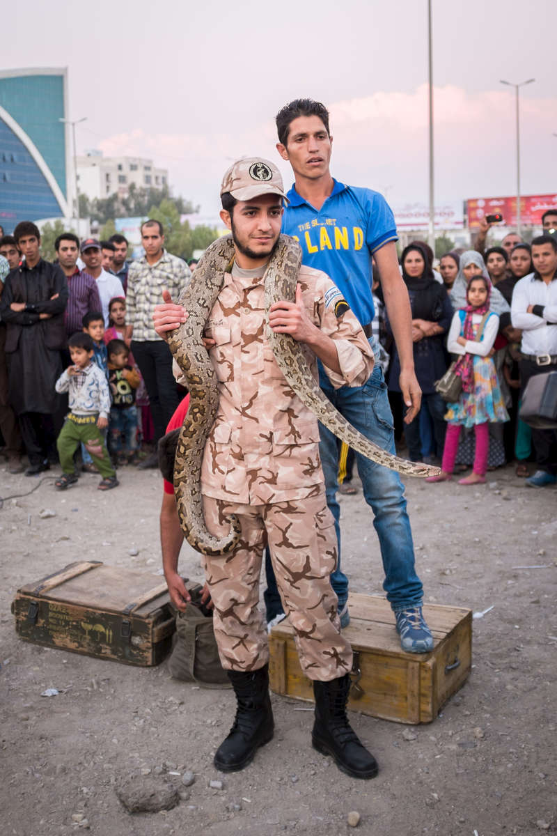 A man in Iranian military uniform at a sideshow in Bandar Abbas.  Military service is mandatory for Iranian men, with the general term 24-months.  Without special exemptions men not completing their service are unable to apply for a driving license, passport, or leave the country without special permissions.