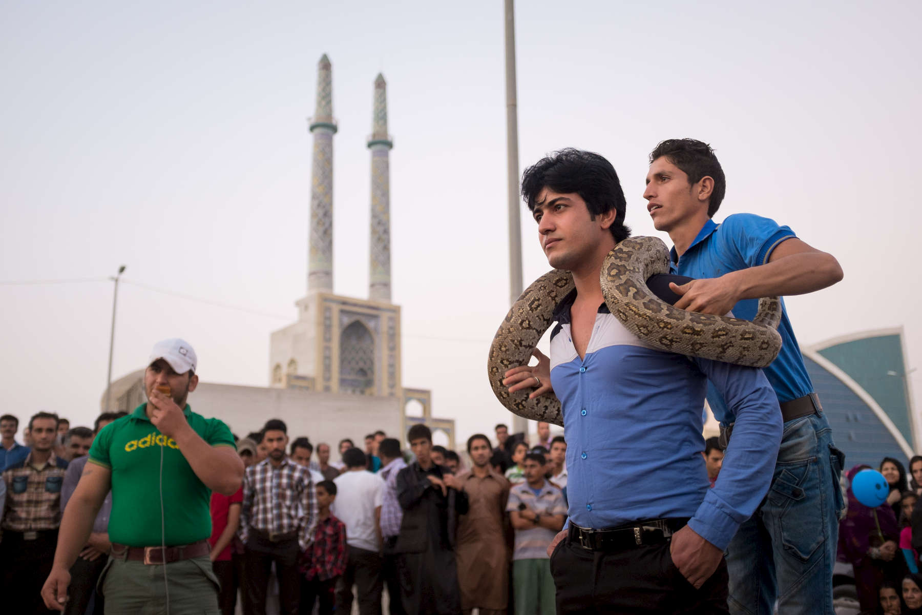 A man looking ill at ease with a large python at a sideshow in Bandar Abbas.  The city is a major smuggling centre; with all manner of goods landing here from Dubai and Oman, just an hour across the Gulf.
