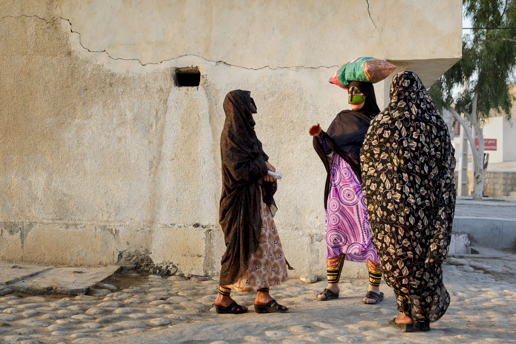 Women in the Persian Gulf port town of Laft, Qeshm Island.  The traditional masks the women wear differ from region to region around the Gulf coast and Islands, with the strong gold/green a feature on Qeshm.