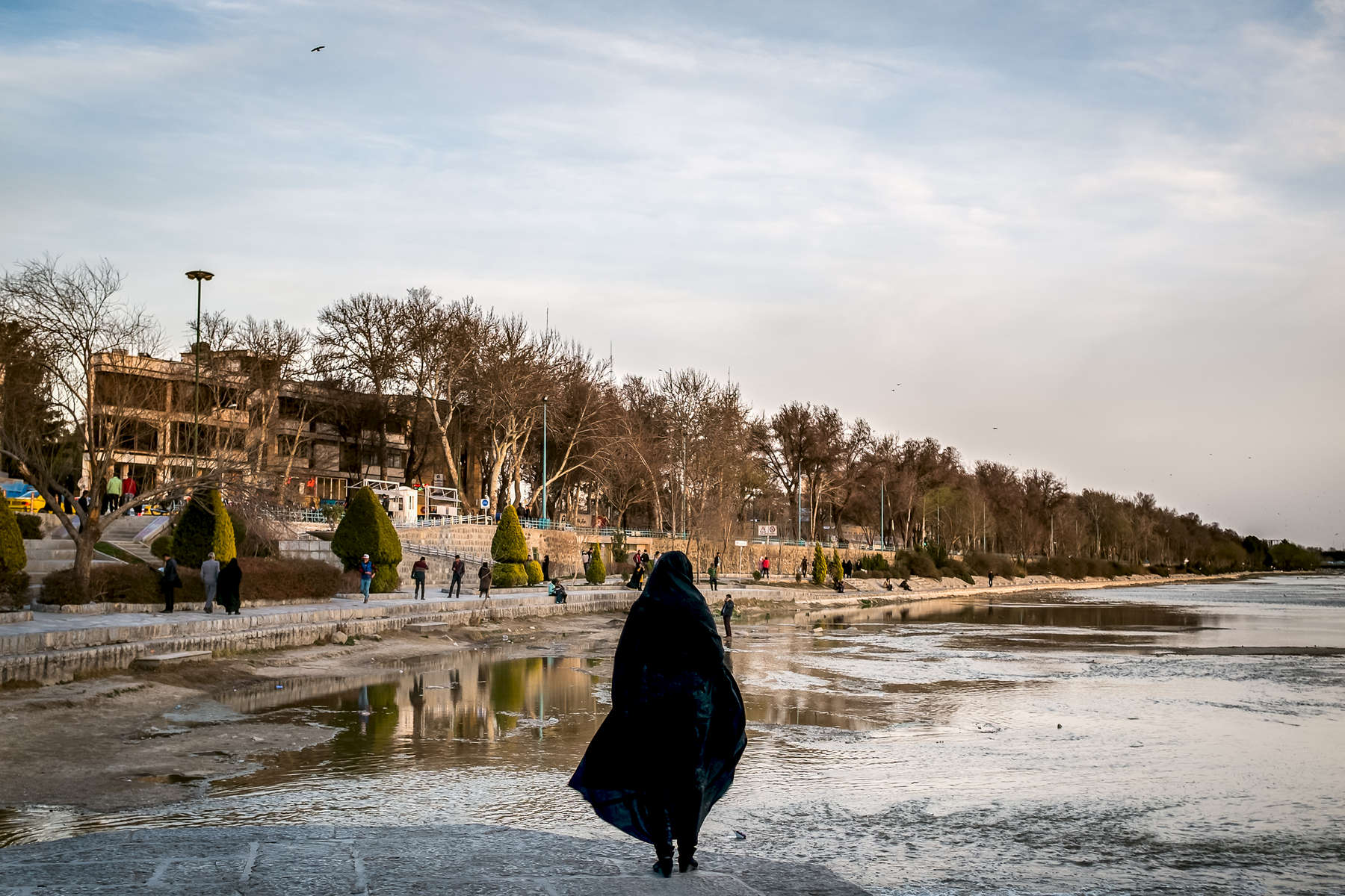 A woman enjoying the view from the foundations of Khaju Bridge, Isfahan. The bridge was built by the Persian Safavid king, Shah Abbas II around 1650 AD1650 AD