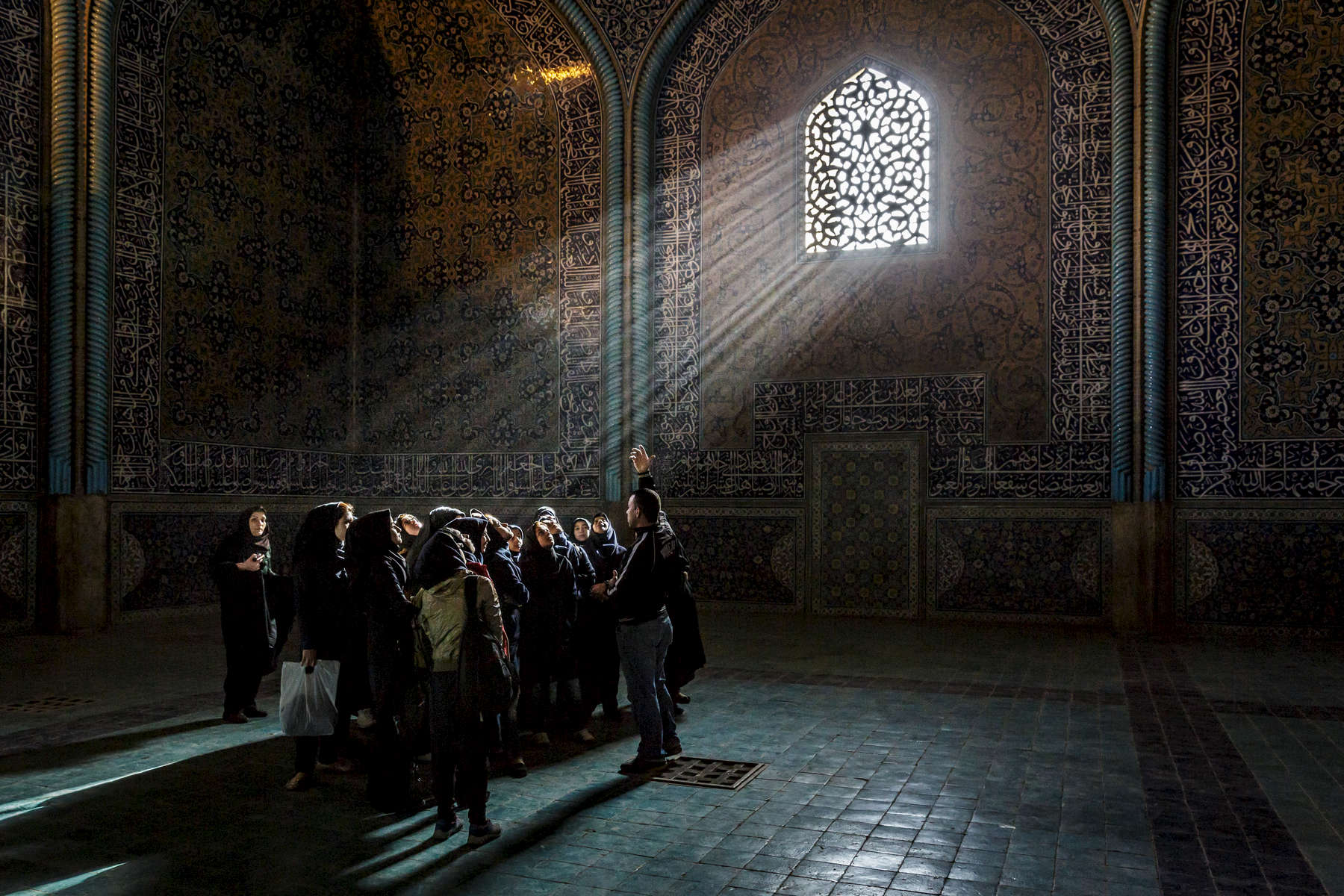 A school group on a tour of the Sheikh Lotfollah Mosque, Isfahan. The Mosque, along with the Naghsh-i Jahan Square on which it borders, are UNESCO World Heritage Sites.  Early mornings see brilliant rays of light illuminate the inticate tile work of the building.