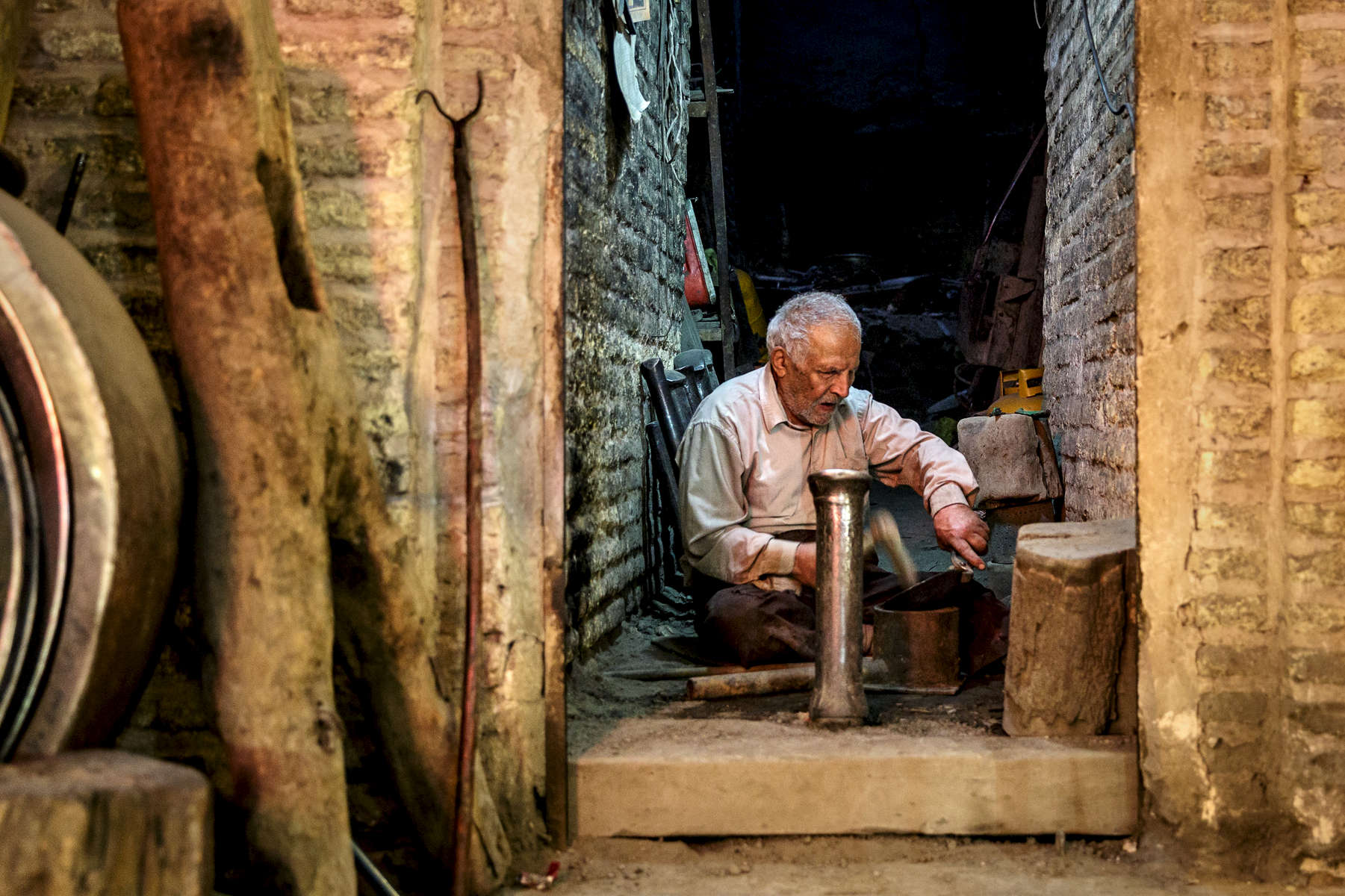 An elderly man making copper pots in Qeysarriyeh Bazaar, Isfahan.