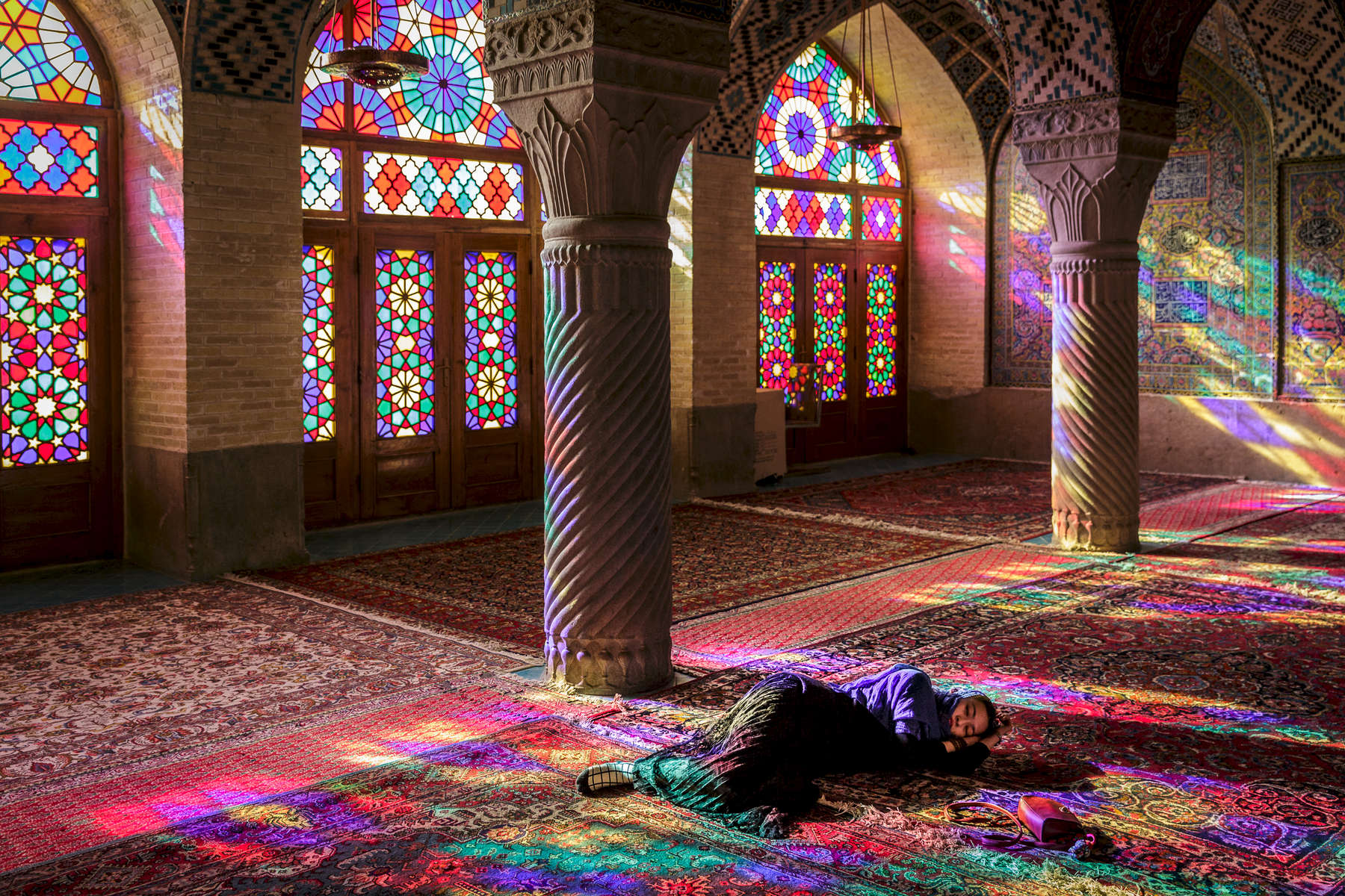 A tourist enjoying a quiet moment in Nasīr al-Mulk Mosque, Shiraz.  Th exterior of the mosque was completed in1888. The Mosque is famous for the early morning light cast through its ornate stained glass windows.
