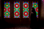 A devotee walks past the magnificent stained glass of the Nasīr al-Mulk Mosque, Shiraz.