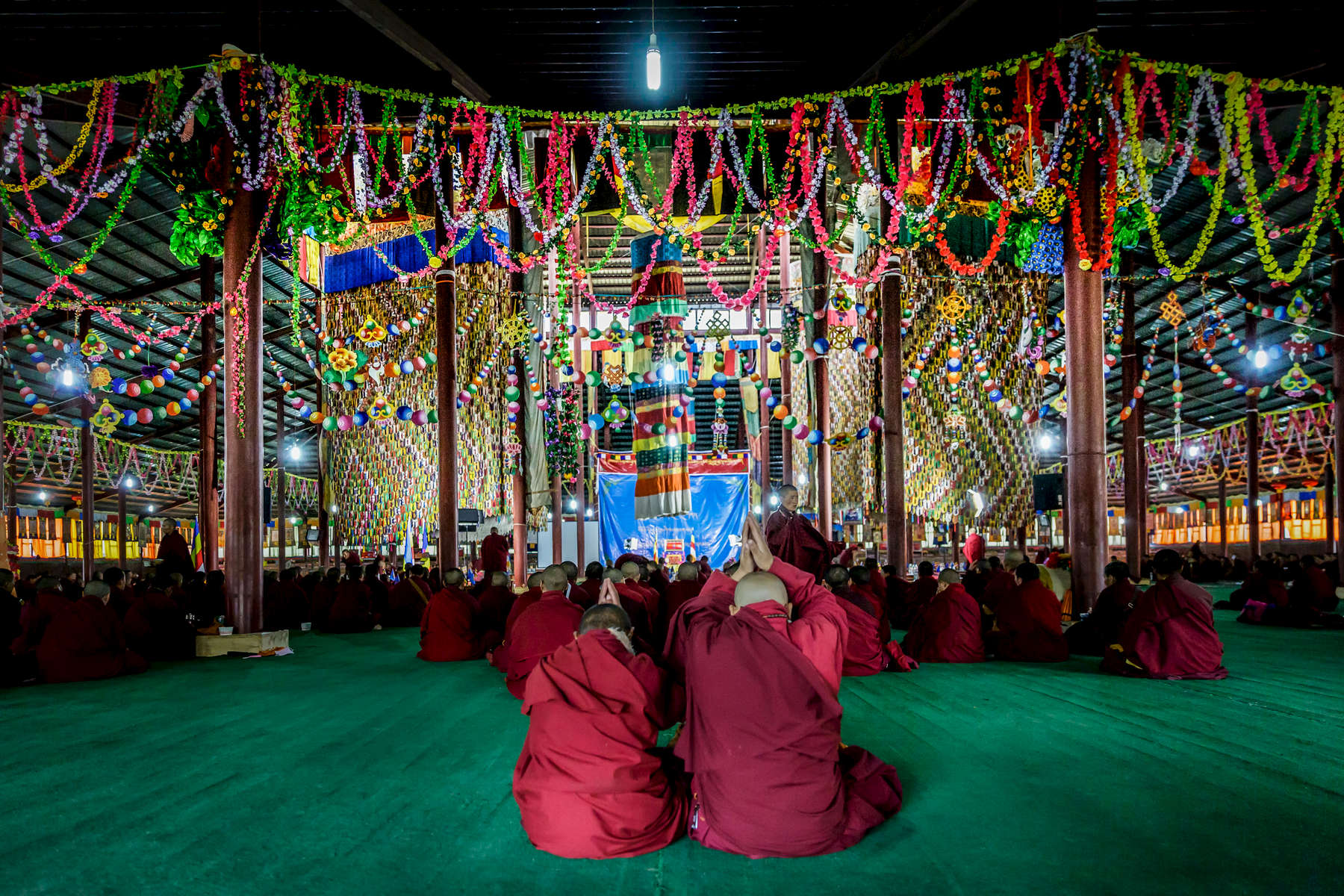 Two young nuns worship at a huge temple in the nuns quater of Yarchen Gar.  On this day young students spent over 10 hours in class, and had the chance to meet the leader at Yarchen, Asong.