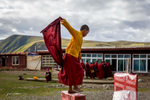 A young nun dancing happily after a 10 hour session of spiritual readings.  Nuns at Yarchen begin their journey at almost any age, with hundreds of young kids living full time on the island.
